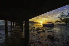 在海滩的美好的日出与停车处在泥a的汽船 库存图片