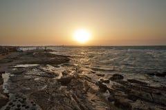 在海滩的美好的日落,惊人的颜色,发光通过cloudscape的光束 阿塞拜疆海和海滩 声音  库存图片