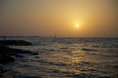 在海滩的美好的日落,惊人的颜色,发光通过cloudscape的光束 阿塞拜疆海和海滩 声音  图库摄影