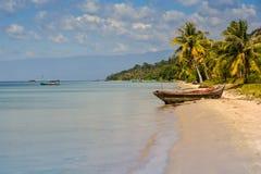 在海滩的老越南渔船由棕榈天蓝色海 库存图片