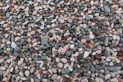 在海滩的色的纹理小卵石 不同的形状和大小石头  免版税库存照片