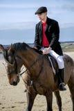 在海滩的英俊的雄性马车手骑乘马在传统衣物 库存照片