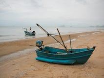 在海滩的蓝绿色乌贼渔船在多云早晨天,有海背景 图库摄影