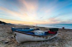 在海滩的蓝色&空白小船在日出 免版税库存图片