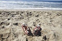 在海滩的被忘记的鞋子 免版税库存照片
