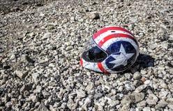 在海滩的被打击的摩托车盔甲 图库摄影