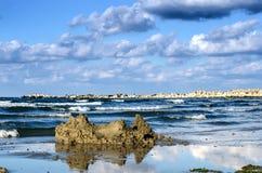 在海滩的被破坏的沙子城堡 免版税库存照片