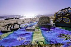 在海滩的赃物与拖鞋帽子风镜和袋子 库存图片