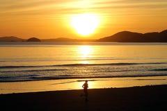 在海滩的赛跑者与日落 库存图片