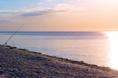 在海滩的钓鱼竿,日出反射了含水表面,天际安静上 在海岸视图之上 库存照片