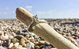 在海滩的钻石婚圆环 库存图片