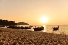 在海滩的长尾巴木小船 免版税库存图片