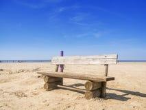 在海滩的长木凳 图库摄影
