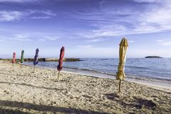在海滩的闭合的颜色伞 库存图片