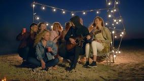 在海滩的音乐晚上,有吉他的愉快的朋友获得乐趣在江边的营火 股票视频