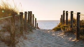 在海滩的风景日落与木篱芭 靠岸的入口在平衡阳光 木专栏和道路在沙子 库存照片