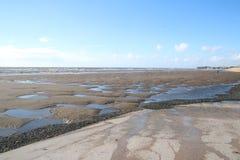 在海滩的风景看法在风暴以后,反射在海滩的水水坑天空 库存照片