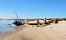 在海滩的马达加斯加人的独木舟与工作的渔夫 免版税库存图片