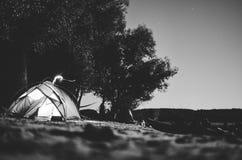 在海滩的黑白帐篷;野营在满月下 免版税库存图片