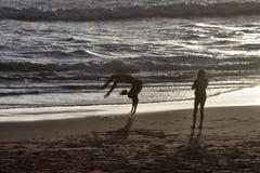 在海滩的Backflips 免版税库存图片