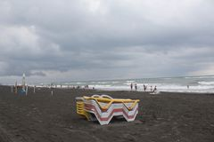 在海滩的Sunbeds 多云天气,海滩的阴暗未认出的人 免版税库存照片