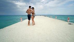 在海滩码头微笑的愉快的夫妇舞蹈 图库摄影