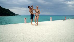在海滩码头微笑的愉快的夫妇舞蹈 库存图片