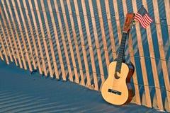 在海滩篱芭的吉他有美国国旗的 免版税库存图片