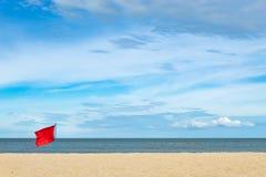 在海滩绣的红旗由海 免版税图库摄影
