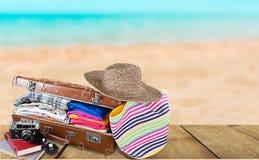 在海滩背景的旅行袋子 库存图片
