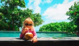在海滩胜地的女孩饮用的椰子鸡尾酒 库存照片