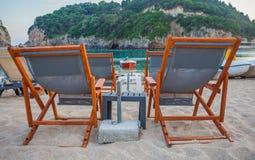 在海滩设定的便携式的懒惰椅子 一个多山岩石在背景中 一架小船和喷气机滑雪为了游人能跳跃  Tro 免版税图库摄影