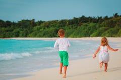 在海滩跑的小男孩和女孩 免版税库存照片