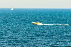 在海滩边附近运输在深蓝色海水的小船 库存图片