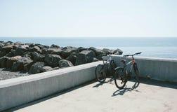 在海滩附近停放的两辆自行车 免版税库存照片