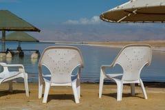 在海滩,世界的最低的咸湖的椅子在海平面下 免版税库存图片