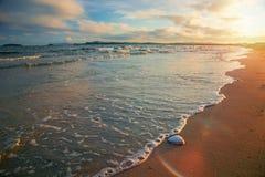 在海滩,在沙子的波浪,壳的明亮的金黄日落 库存照片