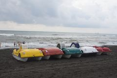 在海滩,阴云密布,云彩的五颜六色的pedalo明轮船,挥动 图库摄影