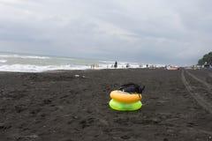 在海滩,阴云密布,云彩的黄色和绿色浮动圆环,挥动 免版税库存图片