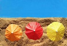 在海滩,顶视图的三把五颜六色的遮阳伞 免版税库存图片