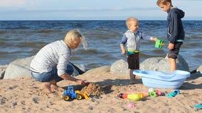 在海滩-有她的使用与沙子的儿子的一个少妇的家庭假日 股票视频