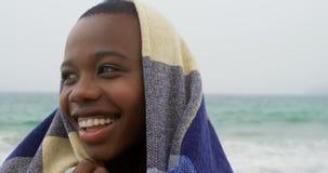 在海滩4k的毯子包裹的非裔美国人的妇女正面图 影视素材