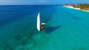 在海热带气候传统单桅三角帆船桑给巴尔的白色风船 免版税库存照片