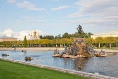 在海王星喷泉附近的人们在状态博物馆蜜饯Peterhof 俄国 免版税库存照片