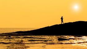 在海现出轮廓站立在岩石的孕妇 库存照片
