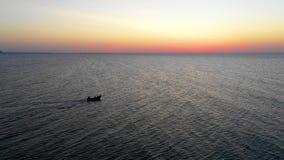 在海的一个小船航行,清早,作为背景的美好的日出 鸟瞰图海景 钓鱼在a的本地人 影视素材