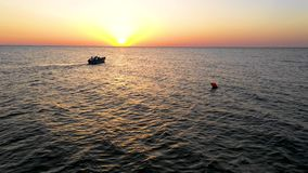 在海的一个小船航行,清早,作为背景的美好的日出 鸟瞰图海景 钓鱼在a的本地人 股票录像