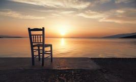 在海的一把偏僻的椅子日落的 免版税库存图片