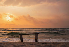 在海的一条偏僻的长凳在日落的沙子的 免版税库存照片
