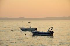 在海的两条小船日落的 库存图片
